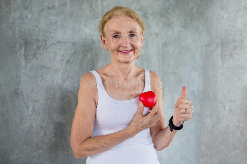 Senior woman holding red heart toy and show Thumbs up  in fitness gym. aged lady exercising.  Old female workout .Mature sport stock photo