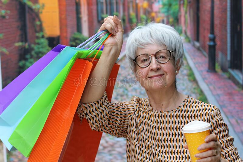 Senior woman holding shopping bags outdoors royalty free stock photography