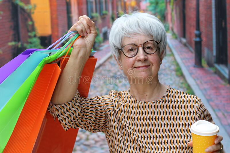 Senior woman holding shopping bags outdoors royalty free stock image