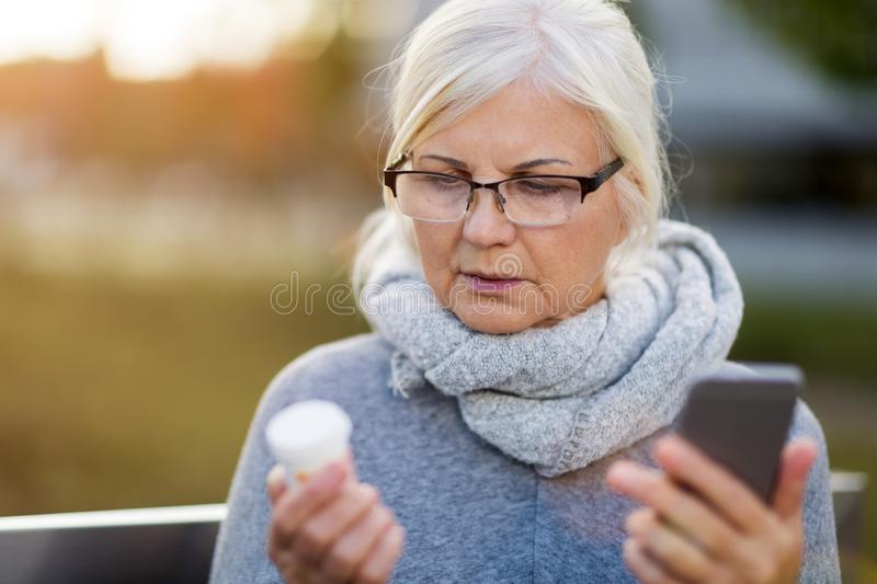 Woman holding smartphone and pill bottle stock photography