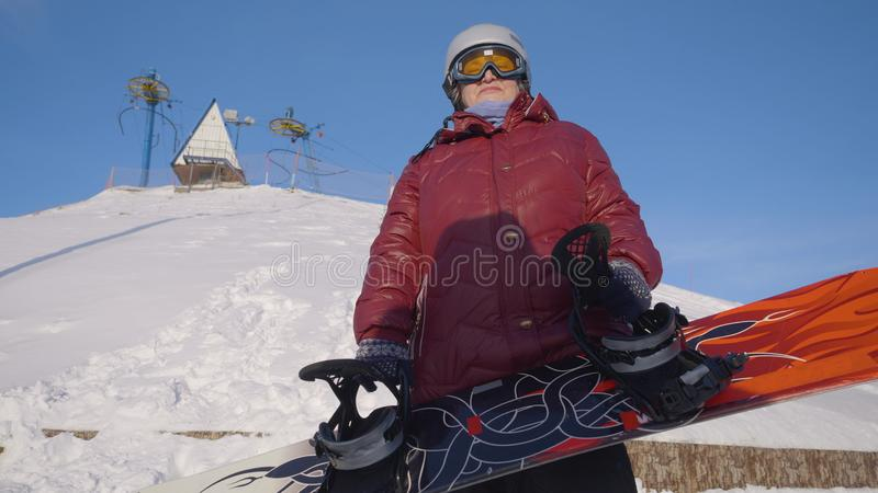 Senior woman holding snowboard. Bottom view happy senior woman in helmet and glasses, wearing ski suit, standing in. Baltimore, USA - January 18, 2019. Senior royalty free stock photography