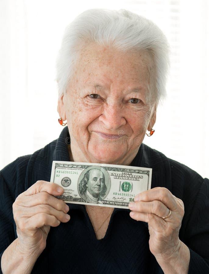 Senior woman holding 100 US dollars banknote stock photo