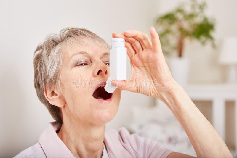 Senior woman holds inhaler stock photography