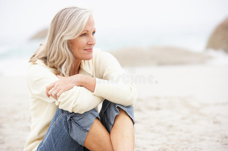 Senior Woman On Holiday Sitting On Beach royalty free stock image