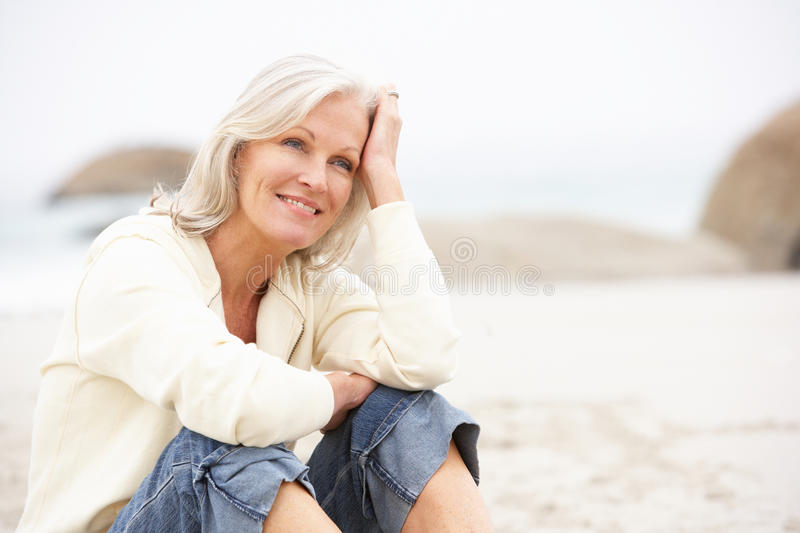 Download Senior Woman On Holiday Sitting On Winter Beach Stock Photo - Image: 15252082