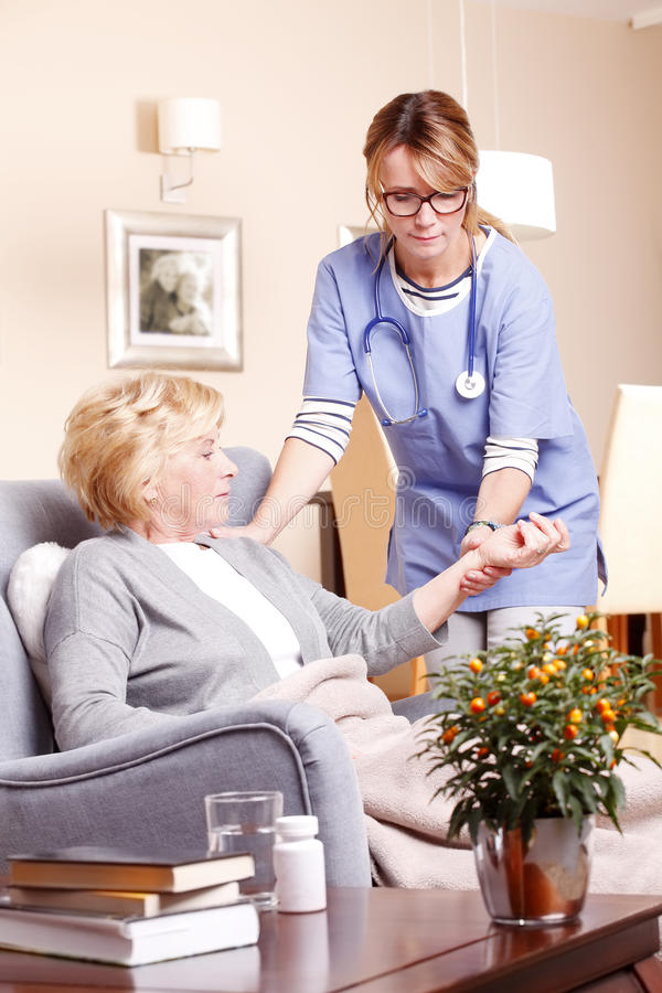 Senior woman with home caregiver. Portrait of senior women sitting at home in living room while caregiver giving helping hand royalty free stock image