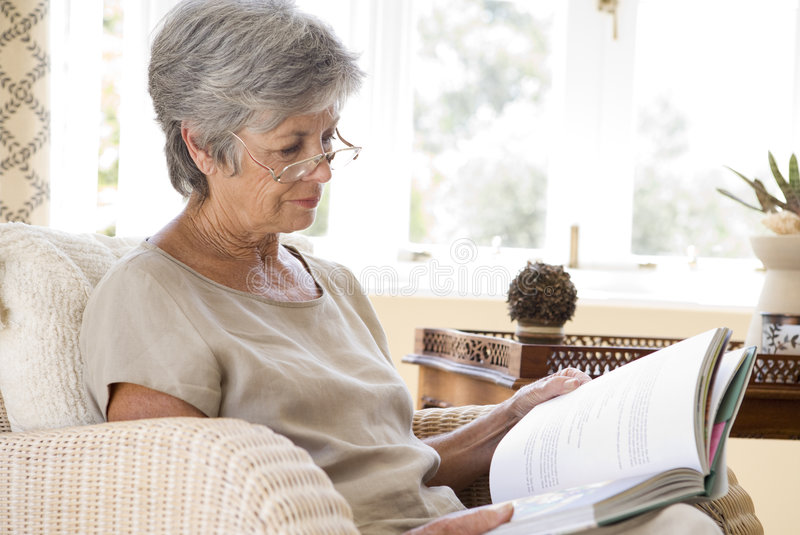 Senior woman at home reading book stock images