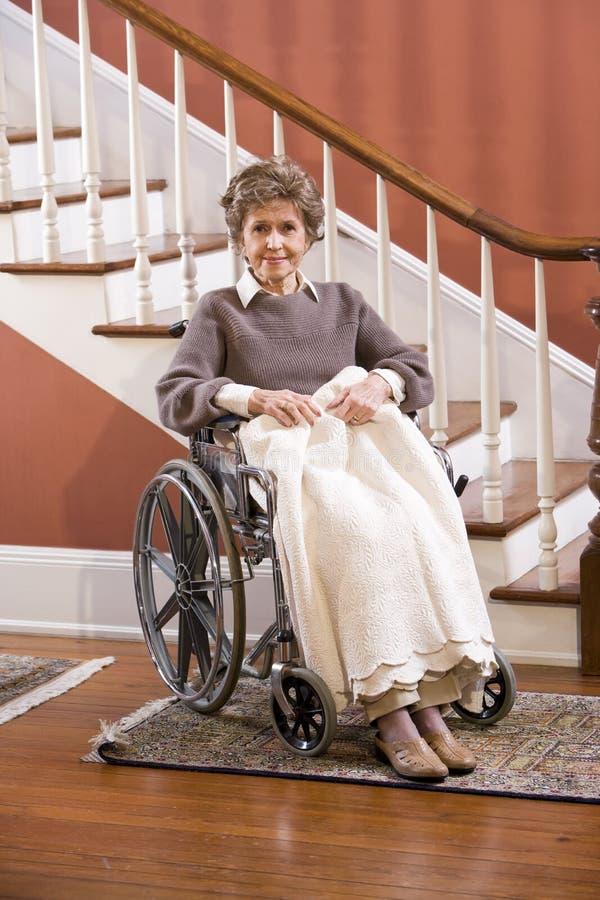 Senior woman at home sitting in wheelchair. Elderly woman in 70s at home sitting in wheelchair stock photo