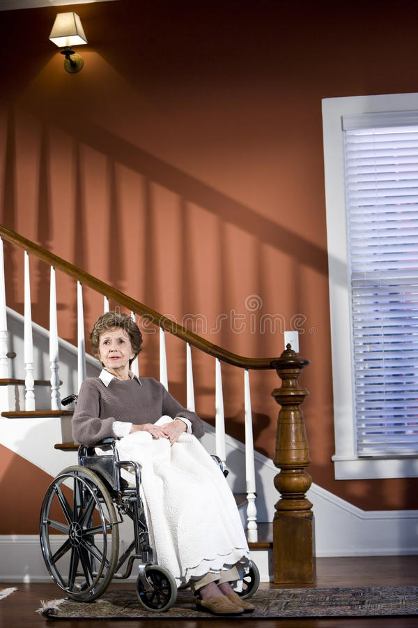 Senior woman at home sitting in wheelchair. Alone stock photo