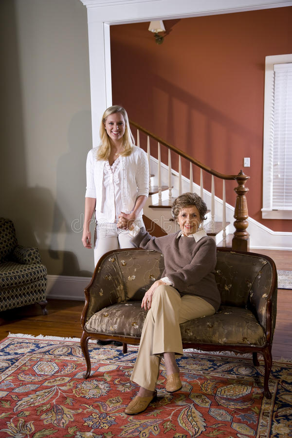 Senior woman at home on sofa with adult daughter. Portrait of senior woman at home on sofa with adult daughter royalty free stock photo