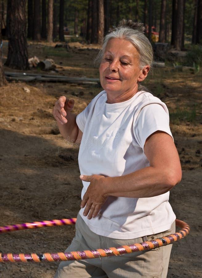 Senior woman hoola hooping. Senior woman enjoying hoola hoop outdoors stock images