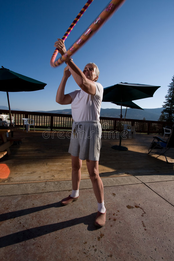 Senior woman hoola hooping. On wooden deck with view royalty free stock photos