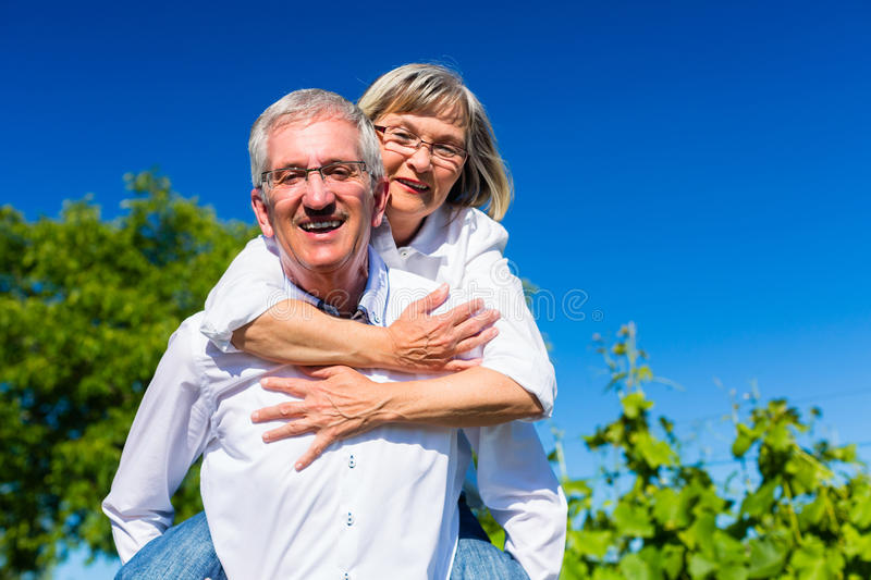 Senior woman hugging her man from behind royalty free stock image