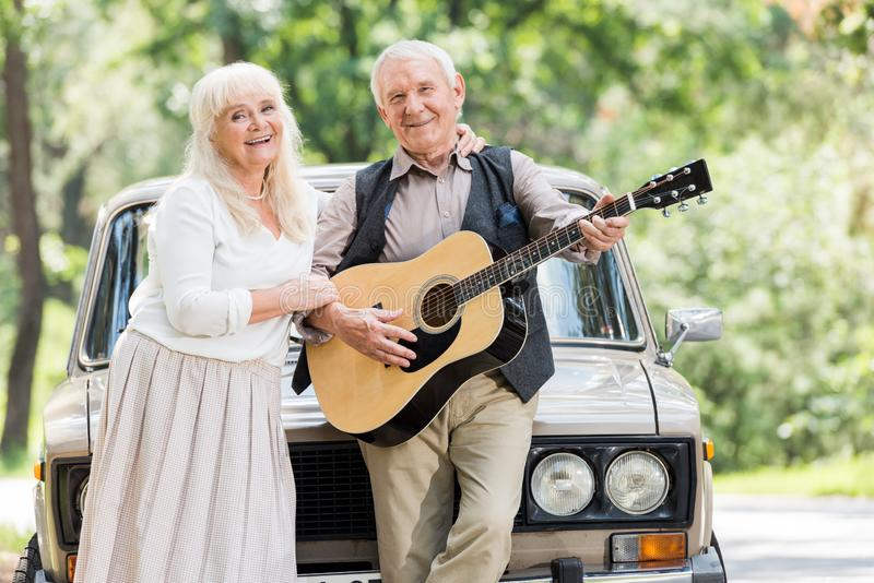 Senior woman hugging man playing guitar against. Beige car stock image