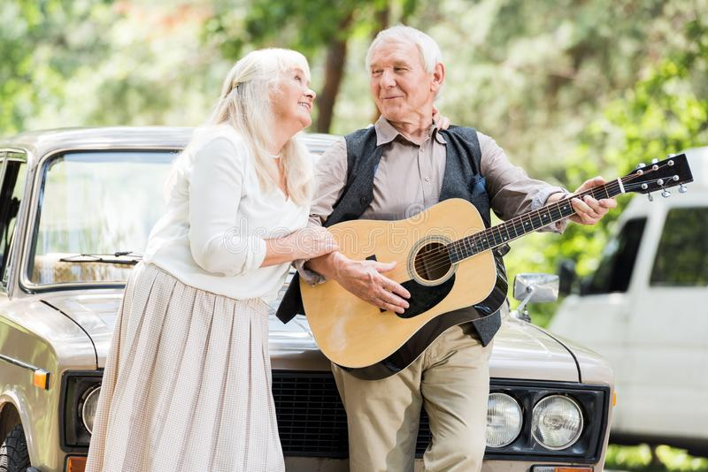 Senior woman hugging man playing guitar against. Retro car royalty free stock photo