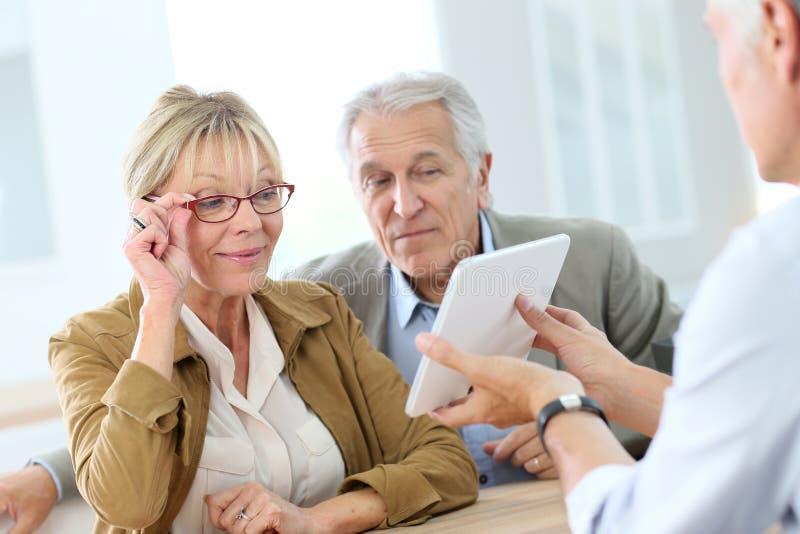 Senior woman with husband in optical store. Senior women at optical store choosing eyeglasses royalty free stock images