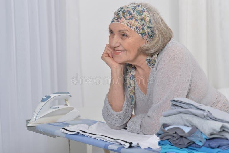 Senior woman ironing. Portrait of a senior woman during ironing royalty free stock photos