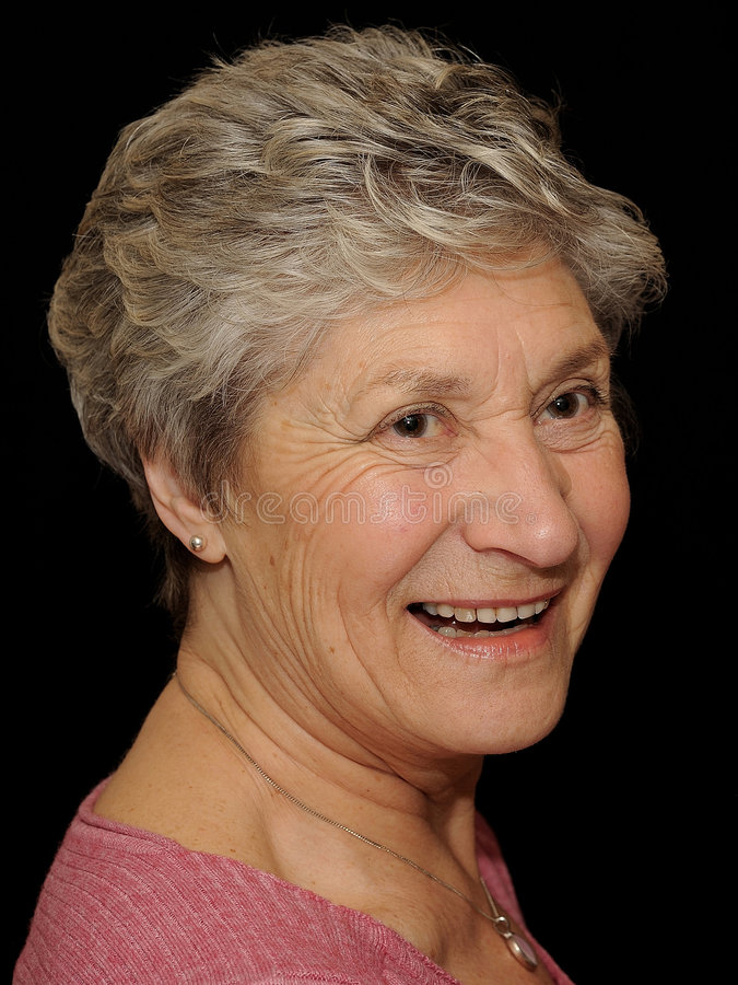 Senior woman isolated on black. Head shot of an older woman with graying hair, smiling, isolated on a black background, caucasian/white stock image