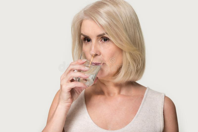 Mature woman hold glass enjoy pure mineral water stock image