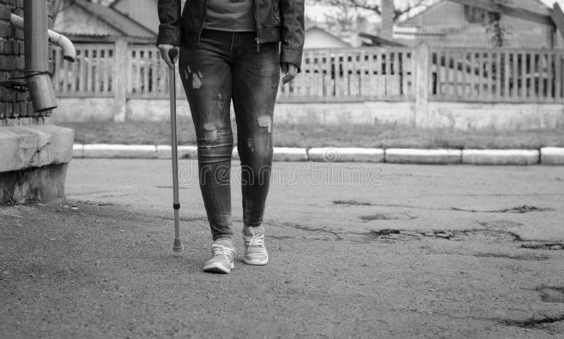 Senior woman in jeans walks with walking cane. Outdoors. Rehabilitation and healthcare concept. Black and white. Copy space stock photo