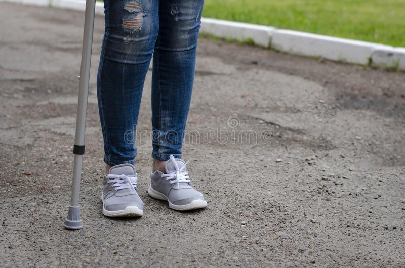 Senior woman in jeans walks with walking cane. Outdoors. Rehabilitation and recovery concept. Copy space stock photo