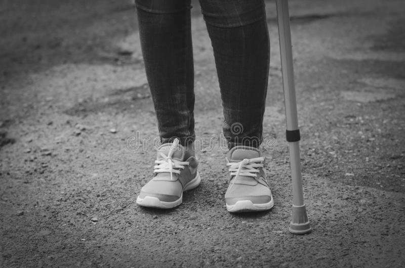 Senior woman in jeans walks with walking cane. Outdoors. Rehabilitation and recovery concept. Black and white. Copy space royalty free stock image