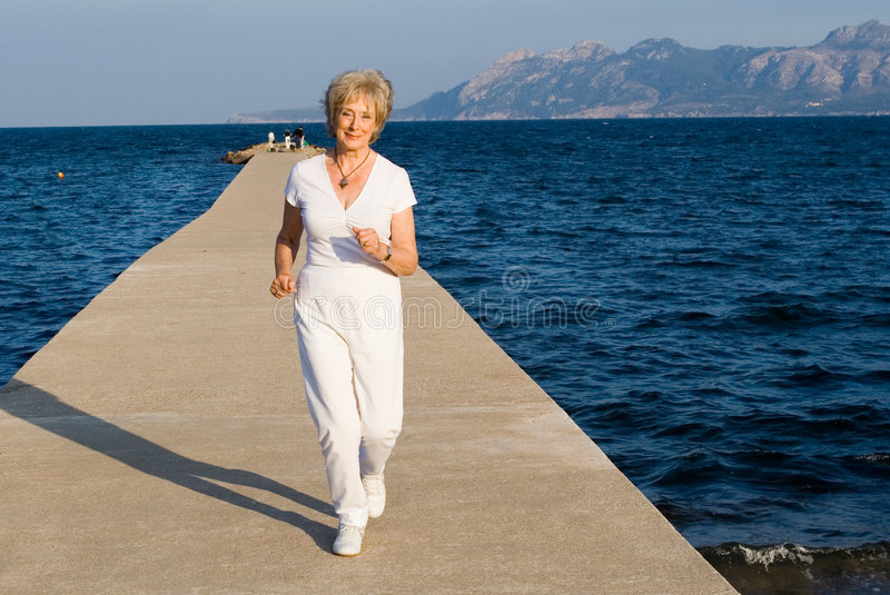 Senior woman jogging royalty free stock photography
