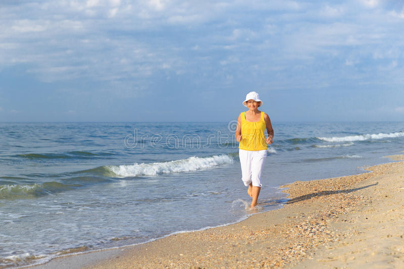 Senior woman jogging on sea beach royalty free stock images