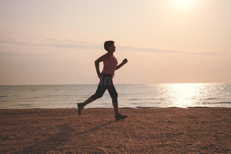 Senior woman jogging on sea beach stock photography