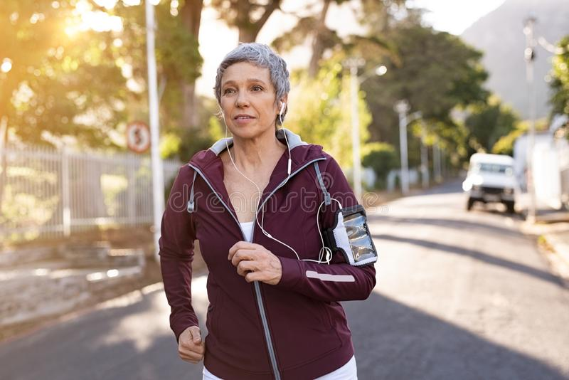 Senior woman jogging in the street stock images