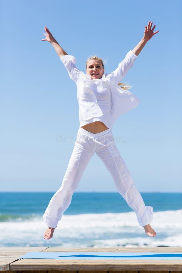 Senior woman jumping. Carefree active senior woman jumping on beach stock photography