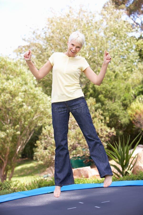 Senior Woman Jumping On Trampoline In Garden