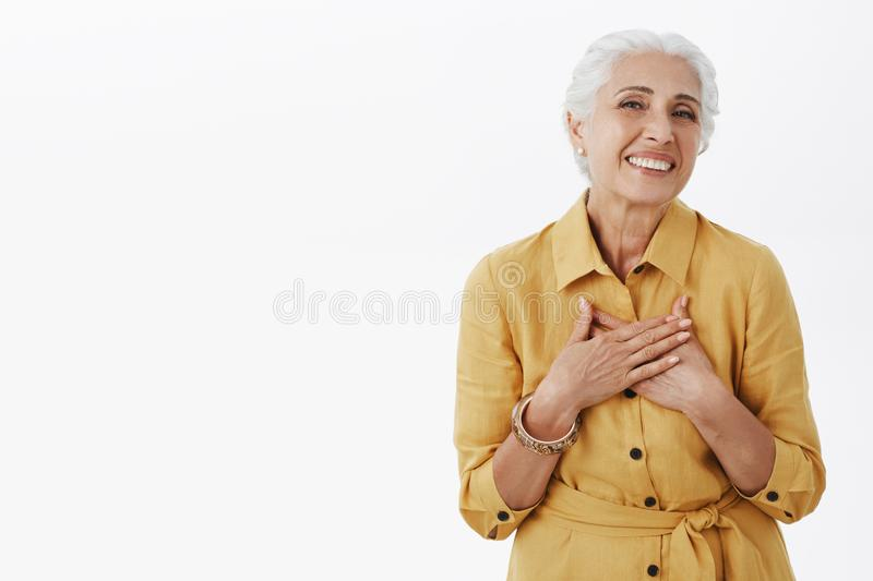 Senior woman keep getting compliments looking fresh and beautiful. Delighted happy charming old lady with white hair in stock image