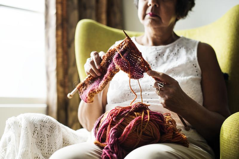 Senior woman knitting at home stock photo