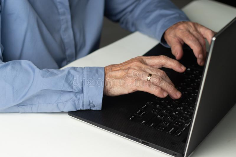 Senior gray-haired woman with laptop. Elderly woman writing memoirs on laptop, searching for information on the Internet or royalty free stock photography