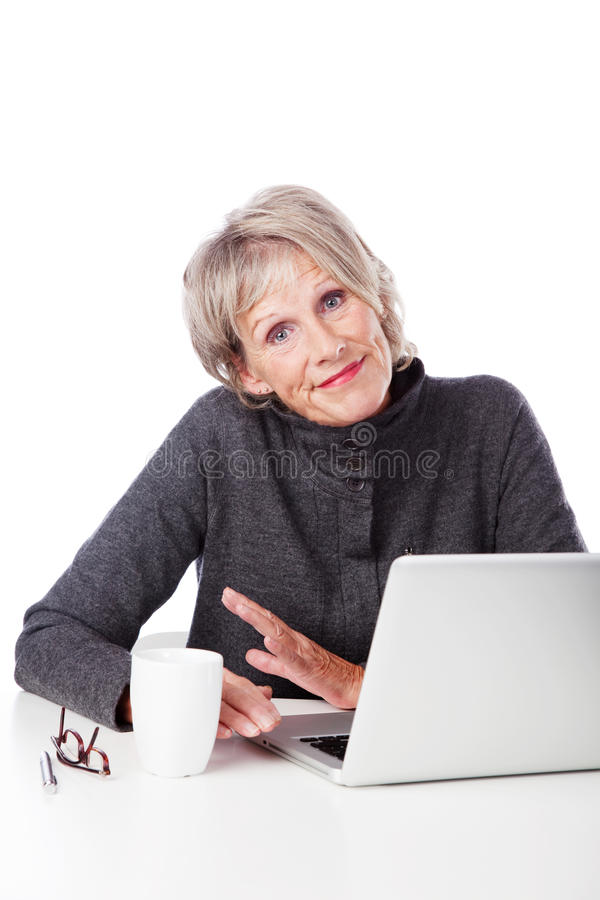 Senior woman with a laptop shrugging shoulders. Attractive grey haired senior woman with a laptop shrugging her shoulders and grimacing showing her ignorance of stock images
