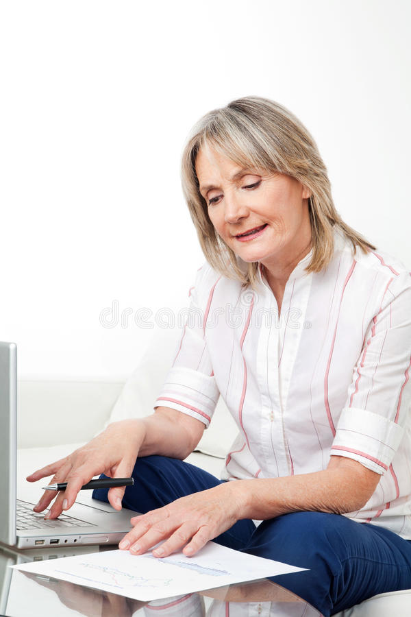 Senior woman with laptop and stock. Happy senior woman working on laptop with stock prices stock photography