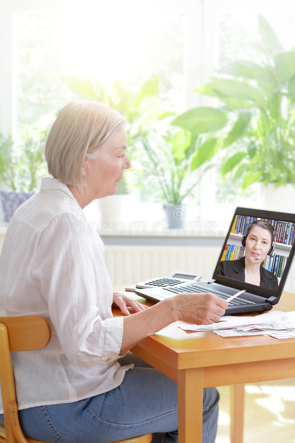 Senior woman laptop tax consultant. Senior women at home with her laptop and lots of receipts, listening to an accountant before making her annual tax stock image
