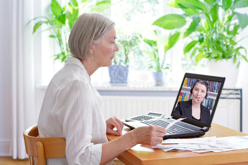 Senior woman laptop tax consultant. Senior women at home with her laptop and lots of receipts, listening to an accountant before making her annual tax royalty free stock photography