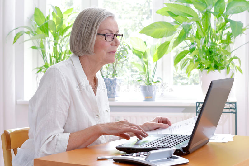 Senior woman laptop tax declaration. Relaxed senior woman at home with a calculator and lots of receipts in front of her laptop making her annual tax declaration royalty free stock photos