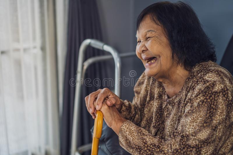 Senior woman laughing and holding wooden cane in living room stock images
