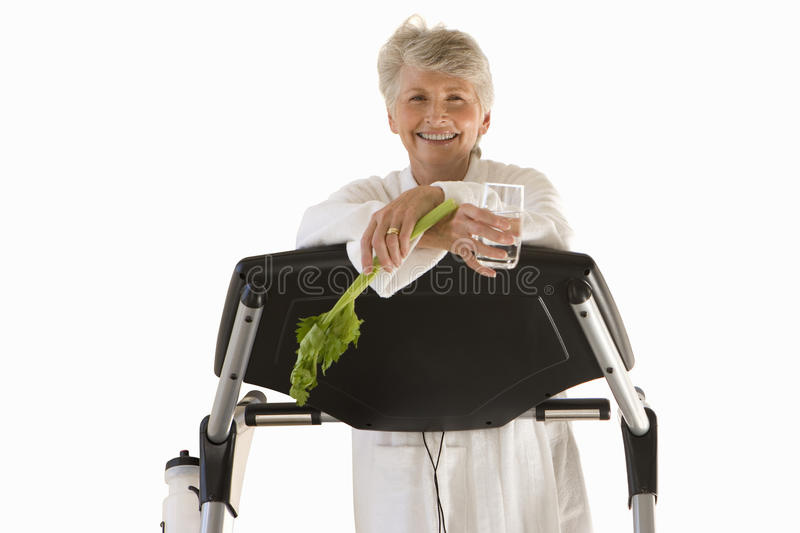 Senior woman leaning on gym equipment in robe, cut out royalty free stock image
