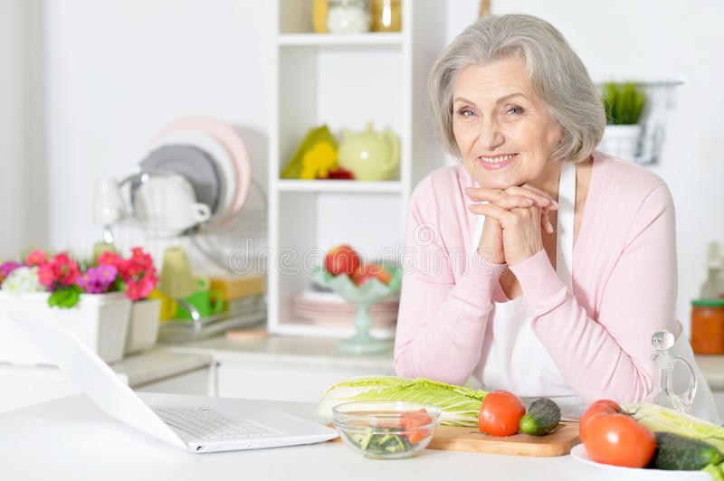 Senior woman leaning on table stock photos