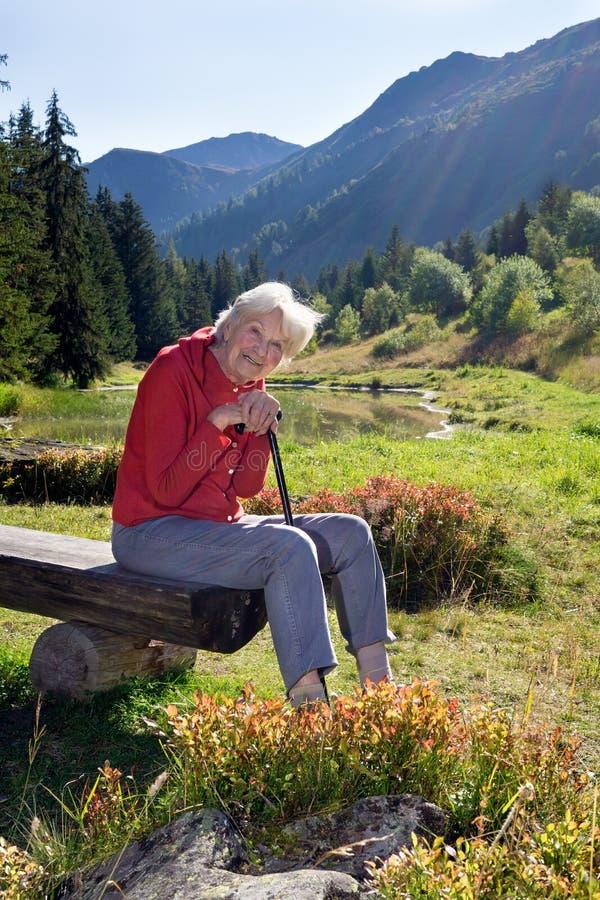 Senior woman leaning on walking steak in the mountains. stock photos