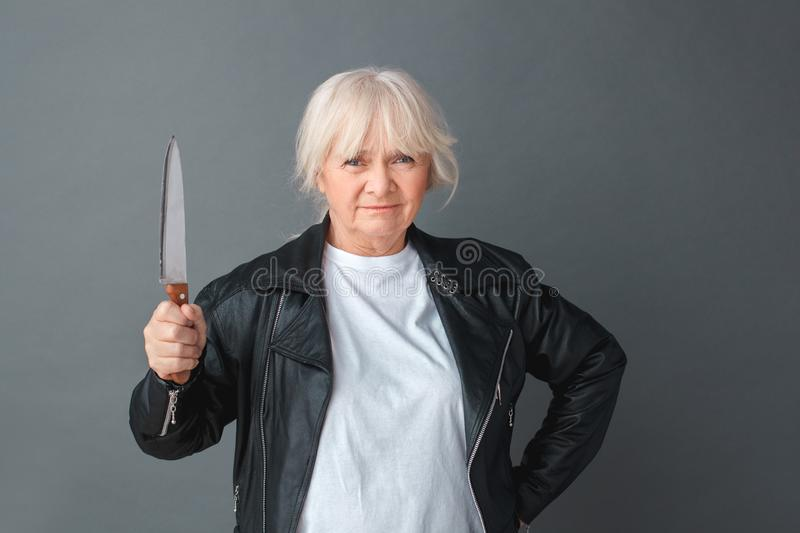 Senior woman in leather jacket studio standing on gray with knife up threatening unhappy stock photo