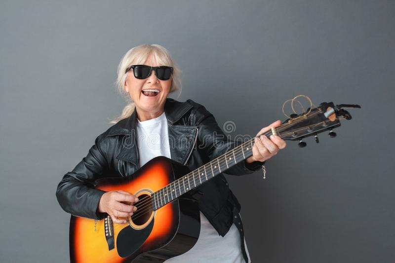 Senior woman in leather jacket and sunglasses studio standing isolated on gray playing guitar smiling stock photos