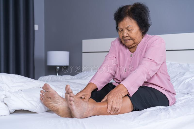 Senior woman with leg pain in bed royalty free stock image