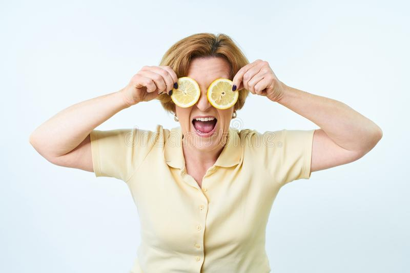 Senior woman with lemon in hand doing funky action. Beautiful woman is covering her eyes with slices of lemon. royalty free stock image