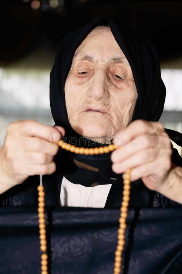 Senior woman looking at beads stock photo