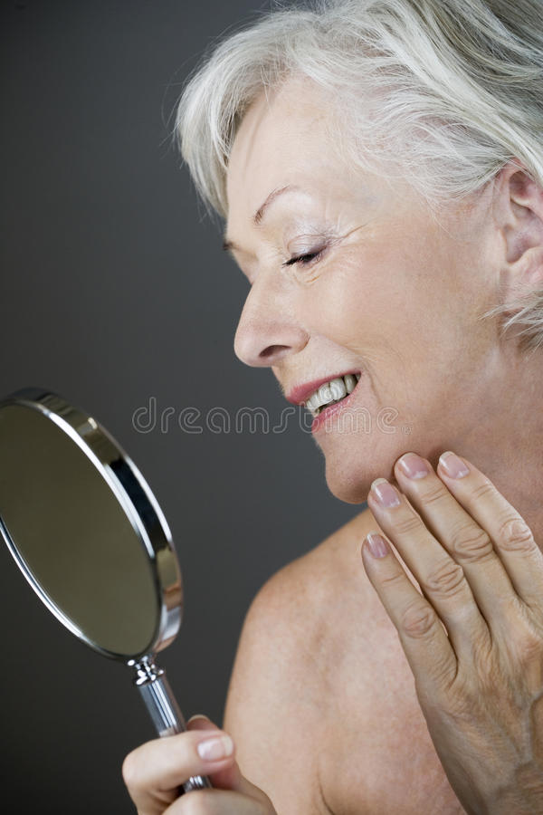 A senior woman looking at her face in the mirror stock photos